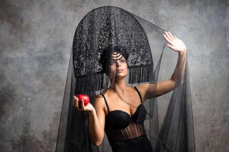 Amazed woman at russian traditional cap hat kokoshnik holding red apple Stock Photo