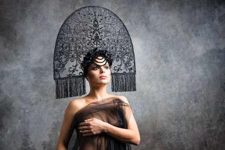 Amazing fashionable charming model posing in Fashion kokoshnik. Unusual perfect brunette woman wearing stylish hat. Cute smile, smoke eyes makeup Foto de archivo - 129996108