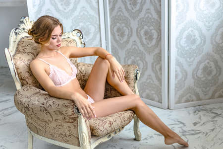 Young, sexy woman with hot body posing in lingerie at luxury interior