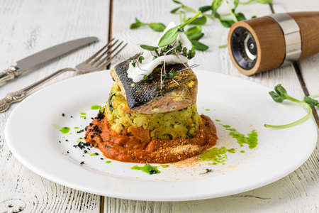 Food - Main course gourmet fish - delicious grilled golden sea bream or dorade with vegetable garnish served on a wooden tabl