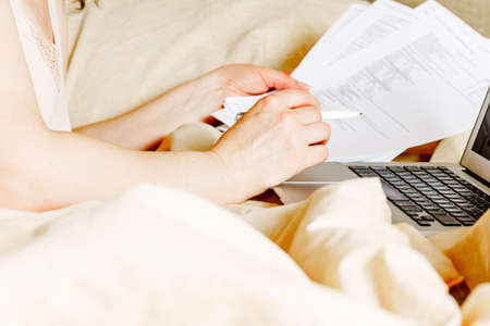 Working woman freelancer in casual clothes with laptop and cup wake up in the bed at home in bright interior stay at home. self-isolation