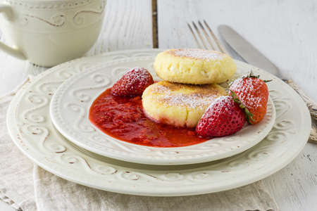 Cottage cheese pancakes (syrniki). Homemade cheesecakes from cottage cheese with sour cream, berries and milk. Traditional Russian dish. Close-up