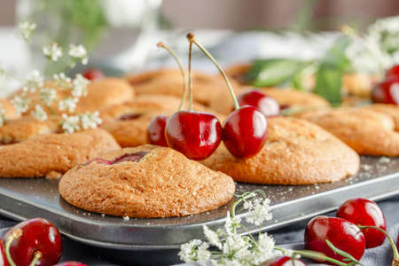 Homemade cherry muffins and fresh cherries on a light background. Delicious dessert