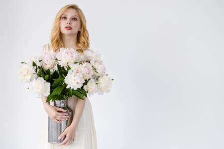 Indoor shot of beautiful girl holding white and rose peonies, winsome woman with big bouquet, enjoying her flowers Imagens