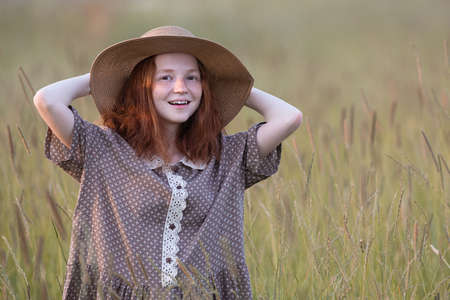 redhead girl posing on a summer meadow at sunset in an elegant dress Banque d'images
