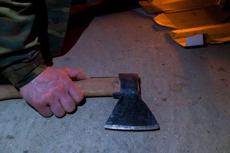 An axe in a workers mans hand near a campfire.