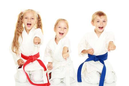 Junge Kinder mit einem Lächeln im Kimono sitzt in einem Ritual darstellen Karateschlag Arm
