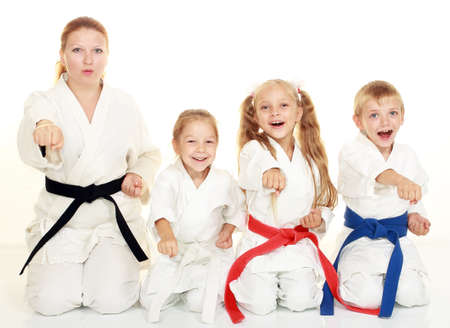 A boy sitting with his sister and mom with her daughter  in a ritual pose karate and beat his fist Фото со стока
