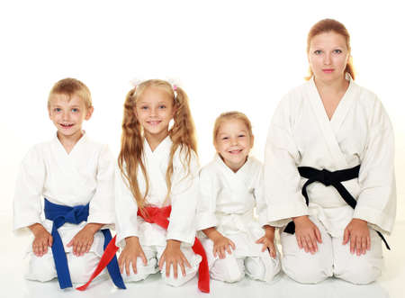 A boy with his sister and mother with her daughter sitting in a karate pose ritual