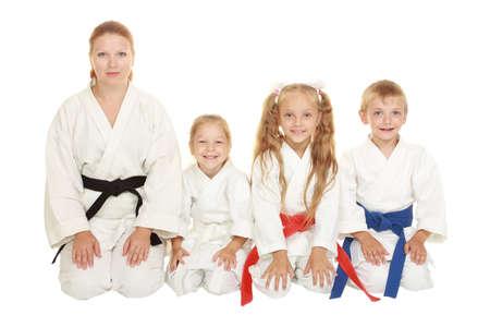 Mutter mit ihrer Tochter und ein Junge mit seiner Schwester sitzen in einem Karatehaltung Ritual Lizenzfreie Bilder