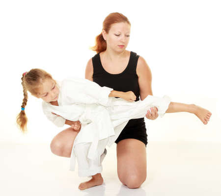Mom teaches daughter punch kicking karate photo