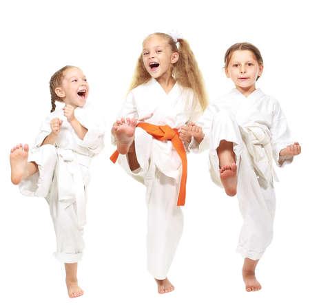 Drei fröhliche Mädchen auf einem weißen Hintergrund in Kimono führen Sie einen Punch Bein