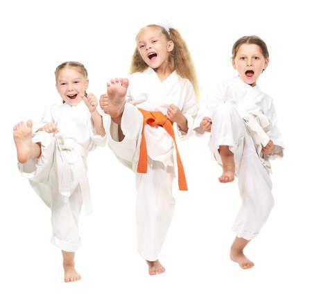 artes marciales: Tres niña alegre, vestida con un kimono blanco pierna retroceso