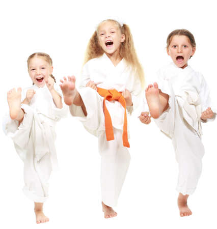 Three girls dressed in white kimono perform punch Фото со стока