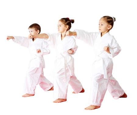 Drei Athleten in einem Kimono auf einem weißen Hintergrund schlagen Punsch Arm Lizenzfreie Bilder