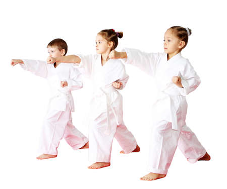karate: Three athletes in a kimono on a white background beat punch arm Stock Photo