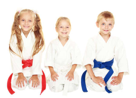 Cheerful young children to sit in a ceremonial kimono karate pose