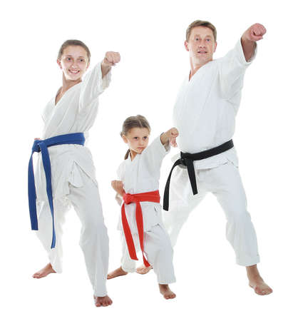 karate: Dad and two daughters in a kimono hitting arm