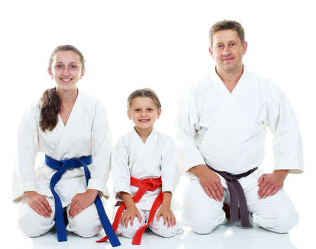 Dad with two daughters sitting in a ritual pose Karate Фото со стока