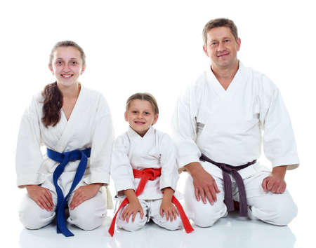morale: Dad with his daughters in kimono sitting in a ritual pose Karate Stock Photo