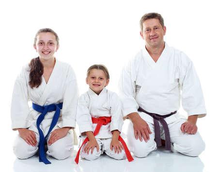 Dad with his daughters in kimono sitting in a ritual pose Karate Фото со стока