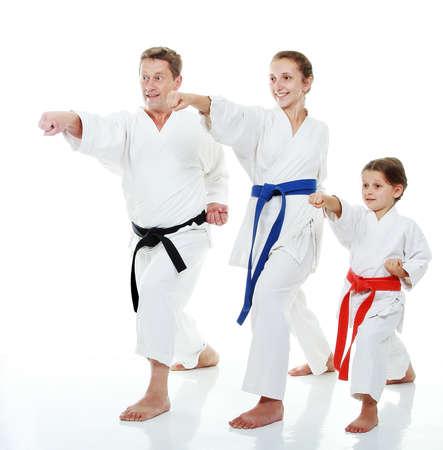 Familie Sportler zwei Schwestern mit ihrem Vater in einem Kimono schlagen Punsch Arm
