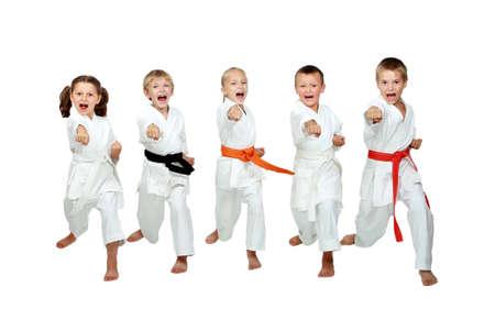 Im Kimono kleine Kinder schlagen ein Karate-Kick Arm