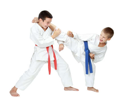 karate boy: Cheerful athletes one beat leg the second makes the block isolated