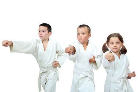 karate: The girl and two boys in kimono beat punch arm