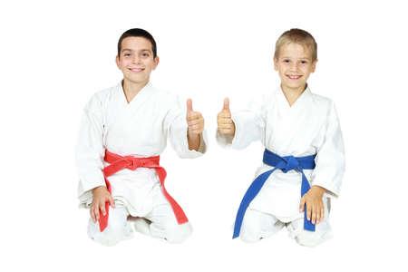 Jungen Athleten sitzen in einem Ritual Pose Karate und zeigen mit dem Finger Super