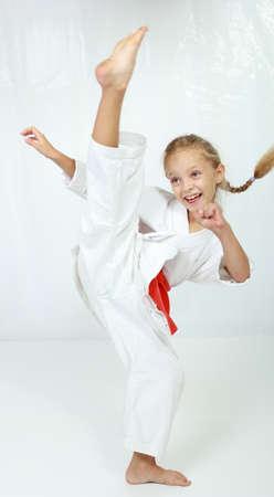 Girl athlete in a kimono performs a kick leg circular Фото со стока