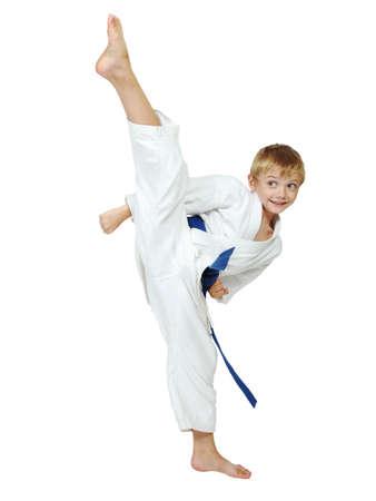 On a white background boy athlete in a kimono performs a kick leg circular insulated Фото со стока