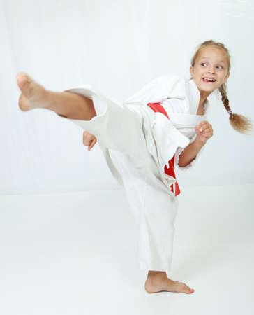 performs: Atleta in un kimono esegue un calcio circolare gamba
