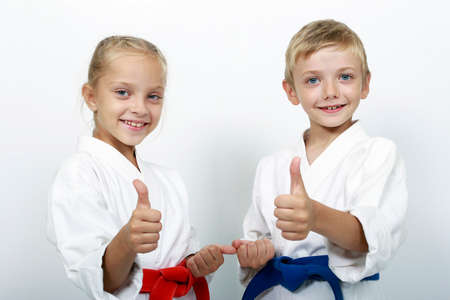 martial art: Children athletes with belts show a thumbs up Stock Photo