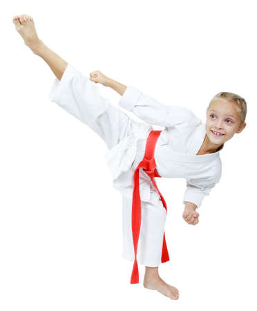 A little girl in a white kimono hits roundhouse kick isolated  photo