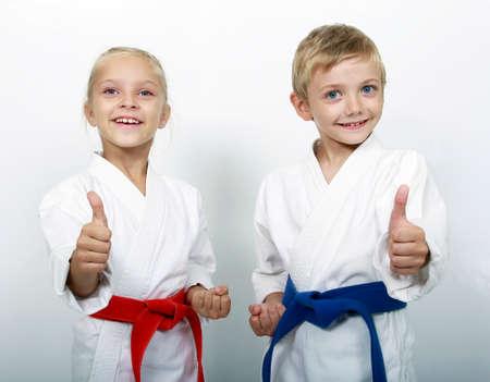 Sporting Bruder und Schwester zeigen Daumen auf den grauen