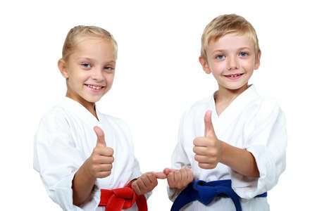 Children athletes with belts show a thumbs up Фото со стока