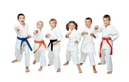 Junge Kinder in Kimono führen Karate-Techniken auf einem weißen Hintergrund
