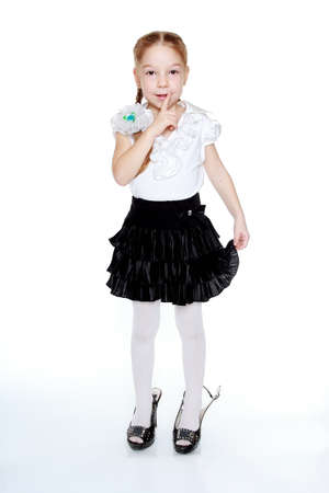 modesty: A little girl in a black skirt and white blouse Stock Photo
