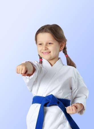 martial art: Cheerful girl with a blue belt beat a blow hand