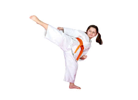 Little sportswoman on a white background beat a high leg kick photo