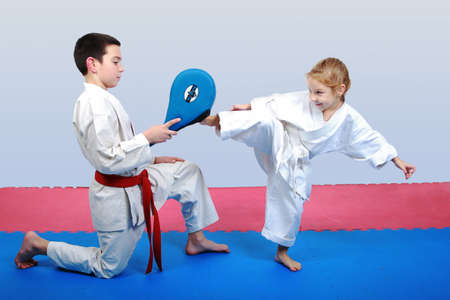 karate boy: Little girl with a white belt beat leg on the simulator in the hands of a boy with a red belt Stock Photo
