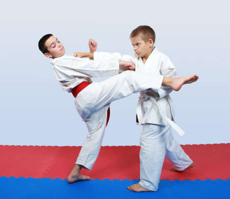 An athlete with a white belt beat a punch in response to kick an athlete with a red belt photo