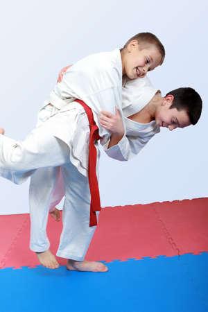 Zwei Jungen mit weißen und roten Gürtel Judo Wurf durchführen