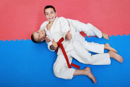 Two young athlete with a red and white belt show finger super photo