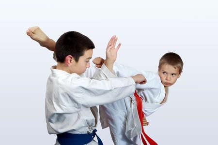defensa personal: Dos atletas con cinturón rojo y azul haciendo huelgas de karate