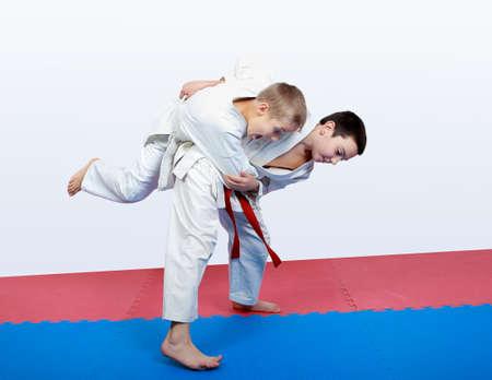 Junge Athlet mit einer roten Schärpe macht Hüftwurf