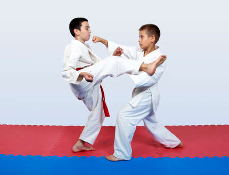 Paired exercises karate athletes with white and red sash photo