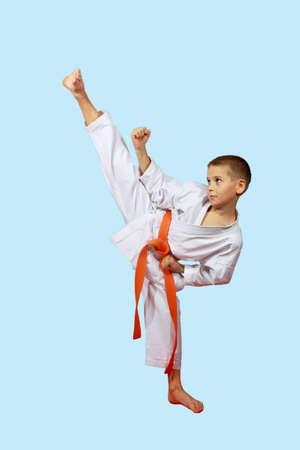Kleine Sportler in einem Kimono führt eine hohe Schlag Fuß