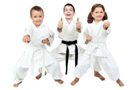 patada: Sobre un fondo blanco los niños pequeños expresan la alegría de clases de karate